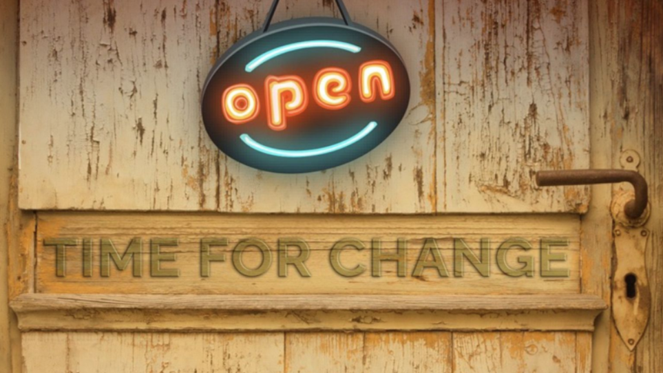 It's Time For Change neon sign on a wooden door